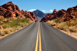 Straigh road into Valley of fire in Nevada with mountains in background
