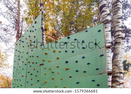 Straight artificial climbing wall with lots of bright hooks for kids and adults in natural amusement Park. Concept of healthy lifestyle, fitness, extreme sports, development of endurance.