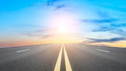 Straight asphalt road and sunset sky