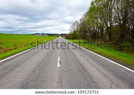 Straight Asphalt Road between Fields  in Belgium - stock photo