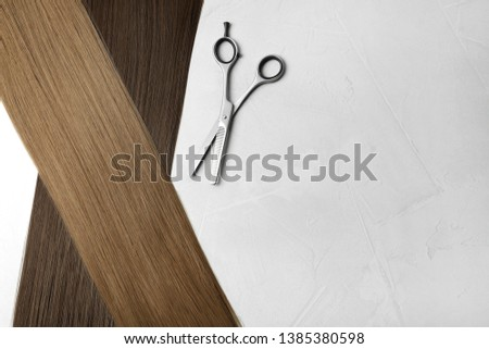Straight brown hair and thinning scissors on light background, flat lay. Space for text