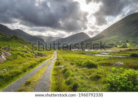 Straight country road leading trough Black Valley, dramatic sky. Landscape with lake, river and MacGillycuddys Reeks mountains, Ring of Kerry, Ireland Stok fotoğraf ©