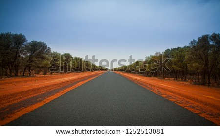 Straight empty open road stretching to the horizon. No lines on tarmac. Red dirt roadside, Outback Australia, Endless travel and Adventure.