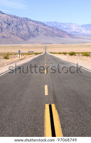 Straight empty road in Death Valley. Nevada, US