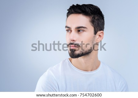 Straight glance. Handsome calm young man being pleased and cheerful while standing against the blue background and looking left