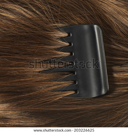 Straight hair fragment with the black comb as a texture background composition