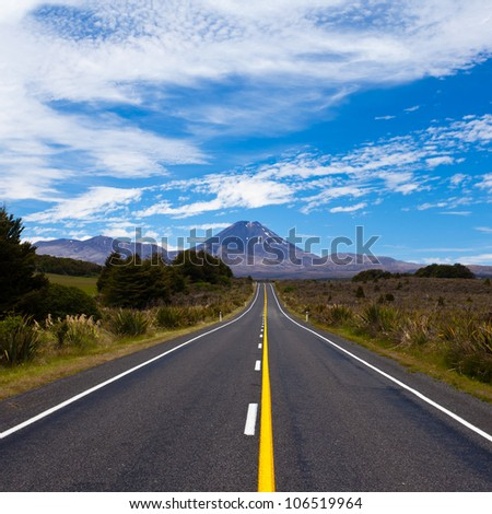 Straight highway leading to active volcano cone of Mount Ngauruhoe in Tongariro National Park, North Island of New Zealand