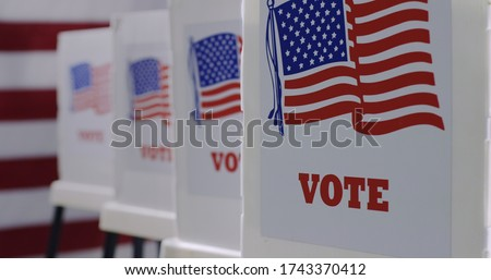 Straight on row of voting booths at polling station during American election. US flag in background.