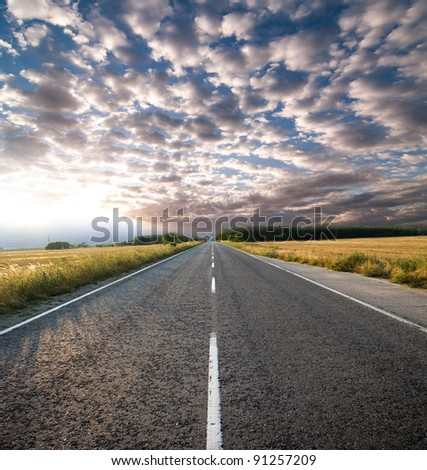 straight road and dramatic sky at the sunset