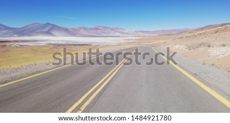 Straight road lost between the horizons of the mountains and the desert #1484921780