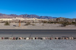 Straight road side with blue sky in Death Valley National Park