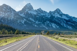 Straight road towards Grand Teton mountains at Grand Teton National Park, United States. Green tress and some light rays can be see coming from the le