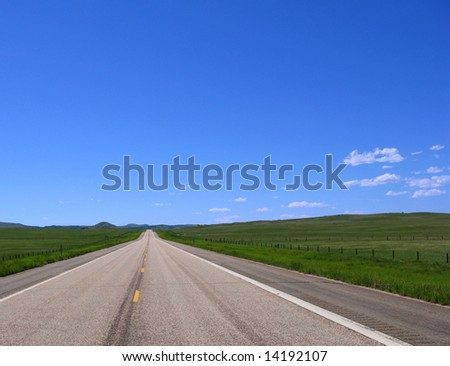Straight stretch of two lane empty country road in wide open prairie and hill landscape in the American West