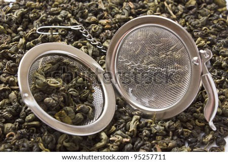 strainer against the background spilled green tea - stock photo