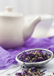 Strainer infuser with loose blue mallow flowers tea on purple cloth with ceramic teapot and cup.