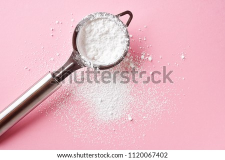 Strainer with powder sugar on pink background, top view