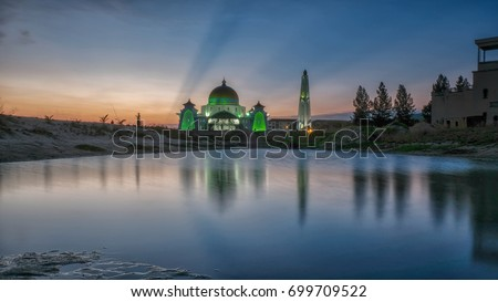 Strait Mosque of Malacca, Malaysia during sunset and beautiful reflection of nature. The Strait Mosque is located at the reclaimed land near Strait Sea. #699709522