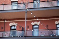 Strand of overhead light bulbs strung in front of a newly renovated brick warehouse building with exterior walkways and stone arched windows