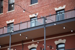 Strand of overhead light bulbs strung in front of a newly renovated brick warehouse building with exterior walkways