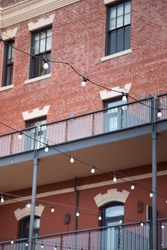 Strand of overhead light bulbs strung in front of a newly renovated multiple story brick warehouse building with exterior walkways