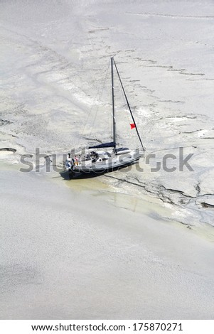 Stranded boat near the abbey Mont Saint Michel waits tide, to set sail. Normandy, France