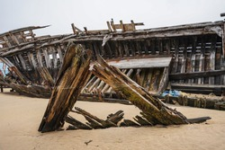 Stranded fishing boats on the beach. Historical wreck in France.
