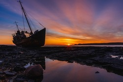 Stranded old fishing schooner at beautiful dawn. The old ship is covered in rust. Rocky coastline of the Barents Sea, Rybachy Peninsula.