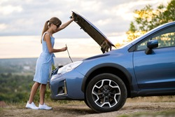 Stranded young woman driver standing near a broken car with popped up bonnet inspecting her vehicle motor.