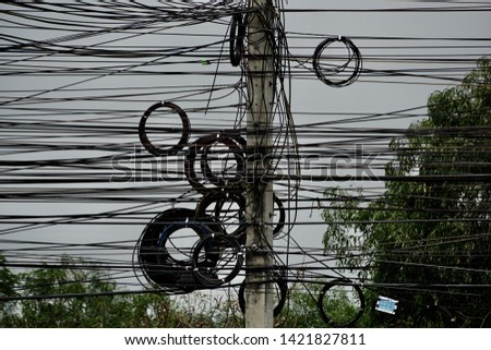 Strange beautiful electric pole. Roll the cable into a loop on the electric pole. The operation of keeping the excess wires to look good on the power poles by the technical staffs. Bangkok Thailand.