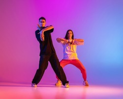 Strange body movements. Two young people, guy and girl dancing contemporary dance over pink background in neon light. Modern dance aesthetics concept