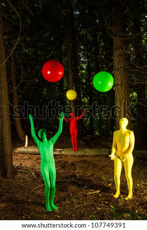 Strange, colorful people playing with balls in a dark wooded forest.