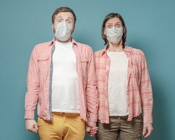 Strange man and woman in medical masks hold hands, they are in a panic and afraid of the epidemic of the virus.