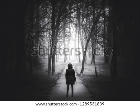 Strange Portal to the other world. Girl goes on the scary road in the paranormal world. Dark mysterious park in a fog. Scary forest lit by moon. Black and white arthouse