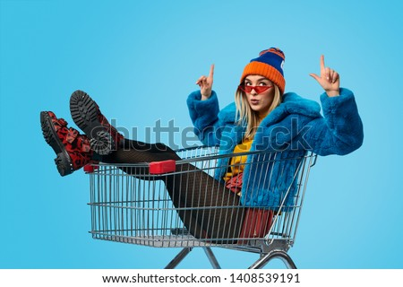 Strange young lady in colorful outfit pointing up while sitting in shopping trolley against blue background Сток-фото ©