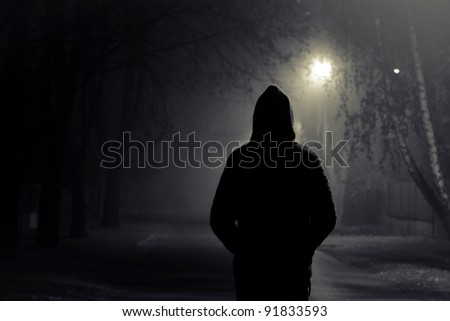 Stranger walking the streets on a cold foggy night