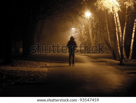 Stranger walking the streets on a cold foggy night. Grain added in postproduction for scarry experience