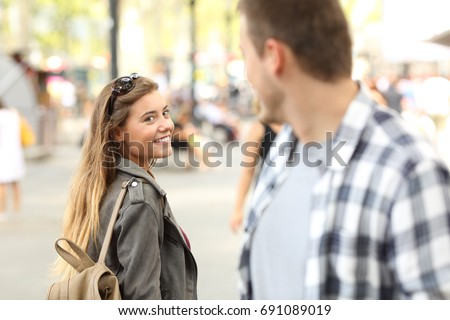 Photo of  Strangers girl and guy flirting looking each other on the street