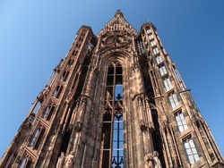 Strasbourg Cathedral (French: Cathédrale Notre-Dame de Strasbourg), also known as Strasbourg Minster, is a Catholic cathedral in Strasbourg, Alsace, France. View on the tower. Blue sky and sunny day.