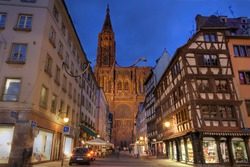 Strasbourg Cathedral (Notre-dame de Strasbourg, France) seen at sunset from the Rue Merciere, a pedestrian-only narrow street leading to the cathedral square.
