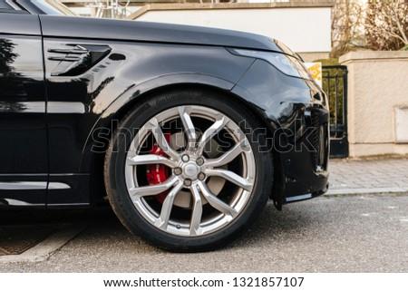 Strasbourg, France - Apr 8, 2018: Detail of the steel rims wheel of Black luxury Land Rover Range Rover Sport SVR parked on the street #1321857107