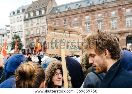STRASBOURG, FRANCE - JAN 30, 2016: Protesting government's plan of the extension of the 'state of emergency' for another three months - holding placard - Emergency State - Racist State, #369659750