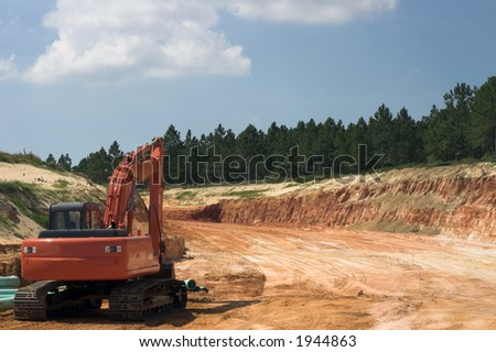 Strata of rock and dirt with heavy equipment on road construction project