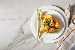 Strata or breakfast casserole with chopped spinach, cheese and soaked overnight cubed bread baked with mustard served on a white plate with cutlery on a white marble background, top view, copy space