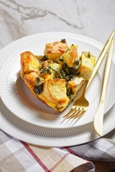 Strata or italian breakfast casserole of spinach, cheese and soaked overnight cubed bread baked with mustard on a white plate with golden cutlery on white marble, top view, portrait orientation