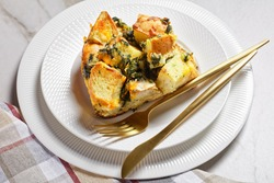 Strata or Italian breakfast casserole of spinach, cheese and soaked overnight cubed bread baked with mustard on a white plate with golden cutlery on a white marble background, top view close-up