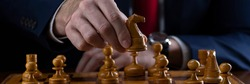 Strategy and business planning concept. A businessman at a chessboard in front of lined up white and black pawns. Strategy and tactics, battle readiness, battle start.