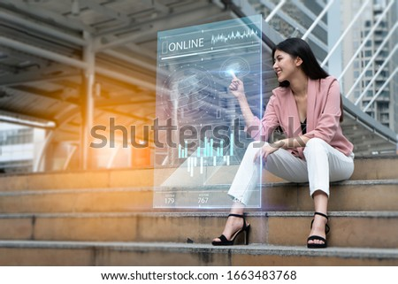 Strategy and digital 5G hologram Concept.Portrait of young Asian woman happy and looking on the digital hologram to expand her business to around the world.businesswoman analyzing growth graph chart.