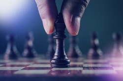 strategy and planning concept, close up human hand while holding or moving king chess piece in cool color tone and light leak effect