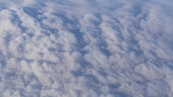 Stratosphere, a view of clouds from an airplane window.  Cumuliform cloudscape on sky. Flying over the land.