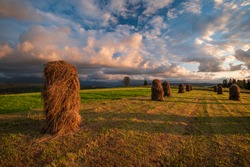Straw bales on a beatiful meadow during sunset under the mountains with beautiful green grass and beautiful clouds in the sky. Tatry, Slovakia, Poland